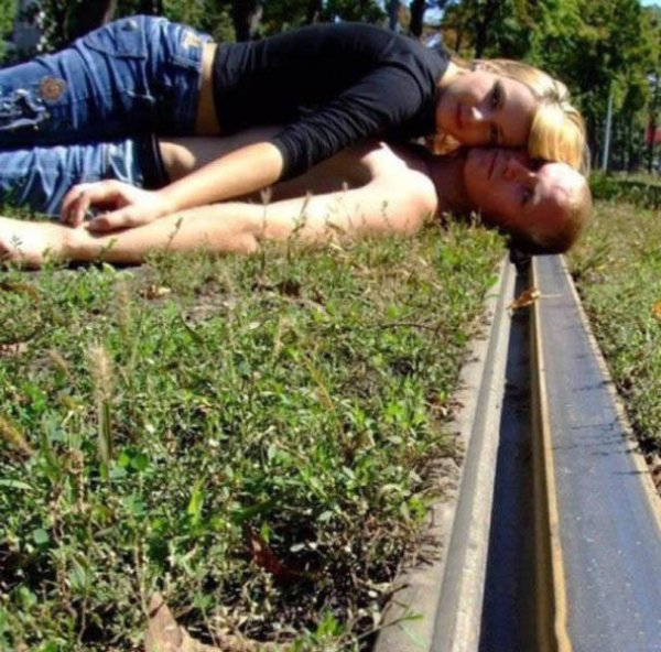 couple laying on the train tracks